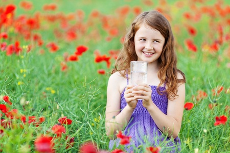 cornfield: Caucasian young girl smiling looking at something while holding a glass of water Stock Photo
