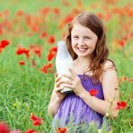 Smiling little child holding a bottle of water over the flower field photo