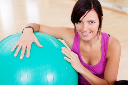 Young woman doing fitness exercise with big ball photo