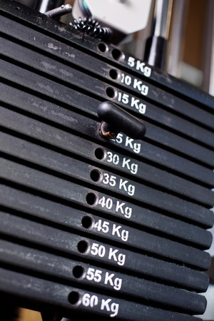 kilos: Close up of weights in a gym with the pin at 25kg