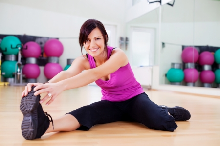 warm up: Young healthy female stretching holding her foot inside the gym Stock Photo