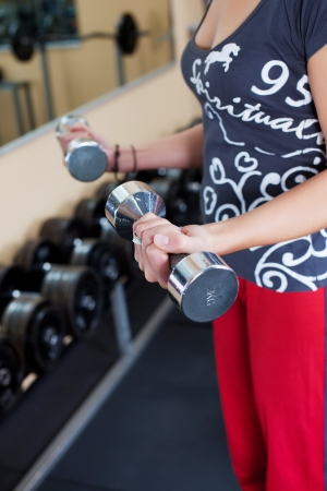 strengthen hand: Young woman using dumbbells in a workout at the gym. Stock Photo