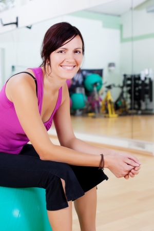 Smiling healthy female sitting on the fitball after work out photo