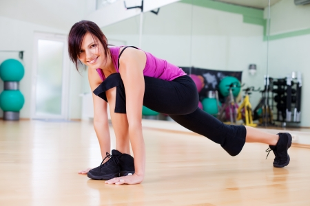toning: Smiling female stretching out her legs and body