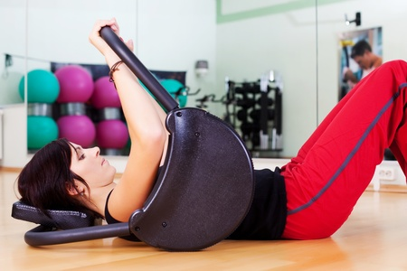 sit ups: Young attractive brunette woman training in the gym focusing on her abdominal muscles