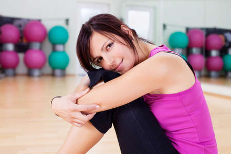 Tired woman resting head on her knees after working out in gym photo