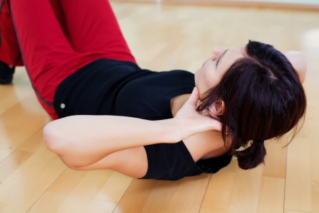 Healthy female lying on the floor and doing sit ups photo