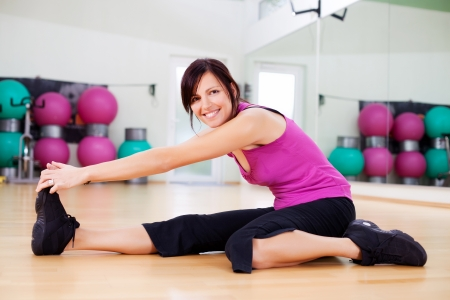 commencing: Athletic woman working out in a gym sitting on the hardwood floor stretching her muscles and warming up before commencing her workout