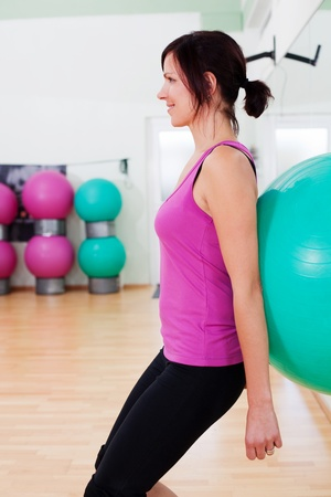 Smiling young woman doing a fitball squat exercise photo
