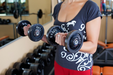 unrecognized: Unrecognized healthy woman exercise with two dumbbells