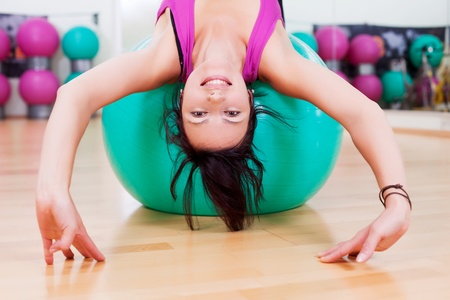 A slim young woman stretching over a fitball photo