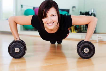 Very sportive woman doing pushups with dumbbells in a gym photo
