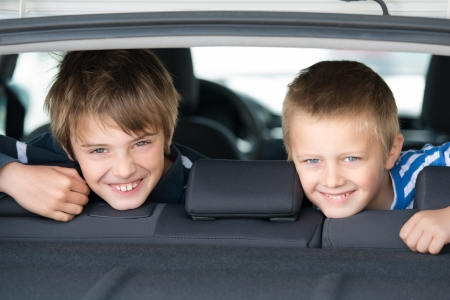 a boy: Portrait of two children smiling inside the car