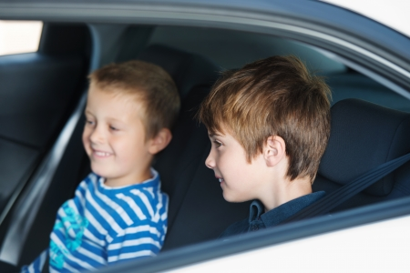 kid portrait: Two children smiling and sitting in the car Stock Photo
