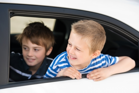 Two little guys inside the car looking out the window photo