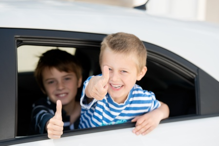 Portrait of two children inside the car showing thumbs up sign photo