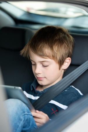 Jonge jongen met behulp van een tablet computer zittend op de achterbank passagiersstoel van een auto met een veiligheidsgordel over zijn schouder