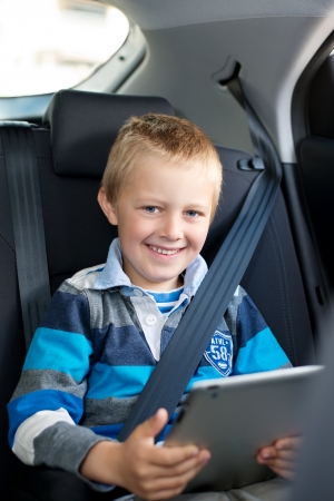 cinturon seguridad: Un niño sentado atado a su asiento en un coche con un ordenador tableta y sonriendo a la cámara