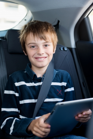 Cute little boy with seatbelt riding in the car while playing tablet photo