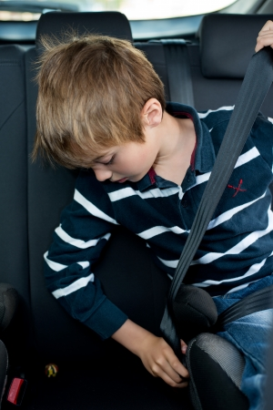 Young little boy buckled up with seatbelt inside the car photo