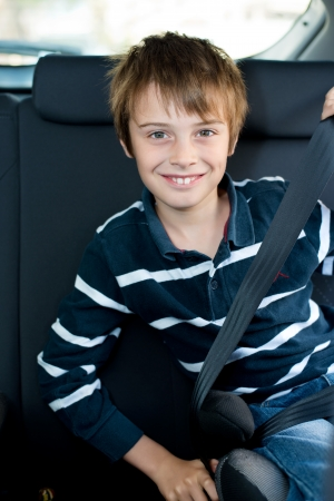 seat belt: Smiling little boy wearing seatbelt inside the car Stock Photo