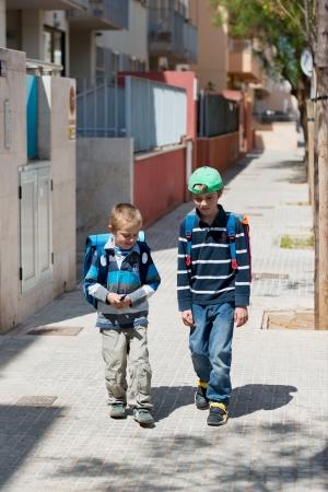 niños platicando: Retrato de dos niños caminando en el camino a la escuela