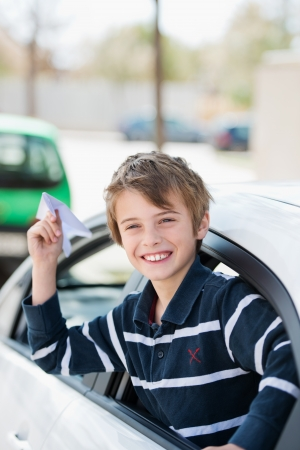 Young man throwing paper airplane out of the car window photo