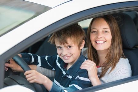 madre e hijo: Hermosa madre enseña a su hijo cómo conducir un coche Foto de archivo