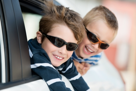 in out: Two little boys with shades playing inside the car Stock Photo