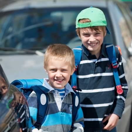 Smiling Schoolchildren waiting for something at the back of parked car photo