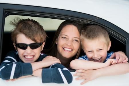 ventana abierta interior: Madre y ni�os que miran por la ventanilla del coche en un retrato feliz Foto de archivo