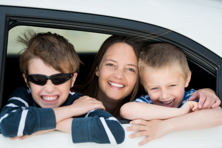 looking out: Mother and children looking out the car window in a happy portrait Stock Photo