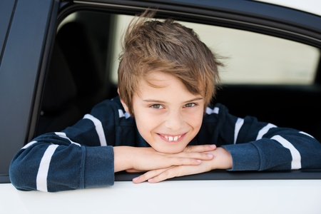 Smiling boy looking out the car in a close up image Stock Photo