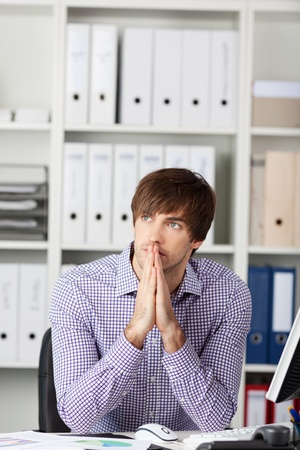 Businessman making gesture with his hands while thinking in office photo