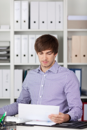 Portrait of handsome young businessman reading paper at desk in office