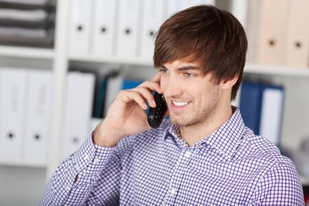 Handsome young businessman using cordless phone in office Stock Photo - 21204128
