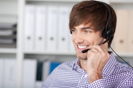 Portrait of smiling handsome customer service executive using headset in office photo