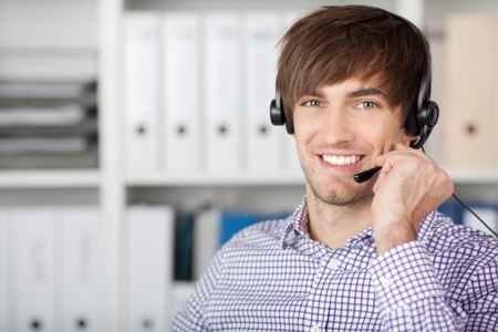 contact center: Portrait of handsome customer service executive using headset in office