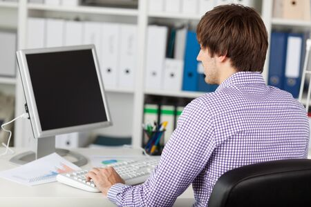 Portrait of young businessman at desk in office photo