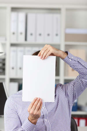 obscurity: Young businessman holding blank paper in front of face in office Stock Photo