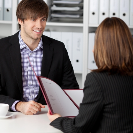 Young male candidate looking at businesswoman taking interview at office desk photo
