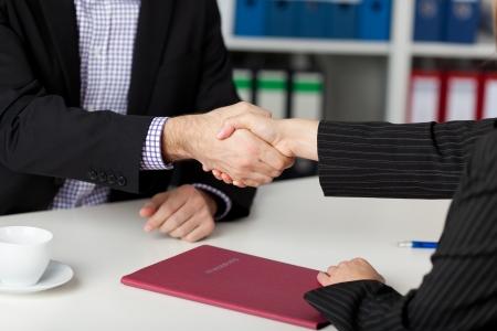 contrato de trabajo: Empresario y empresaria agitando las manos en el escritorio de la oficina Foto de archivo
