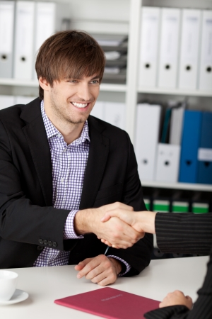 Successful job interview - happy businessman shaking hand and smiling. photo