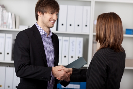 Businessman and businesswoman shaking hands in office Stock Photo - 21199731