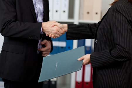 Young Businessman and businesswoman shaking hands in office photo