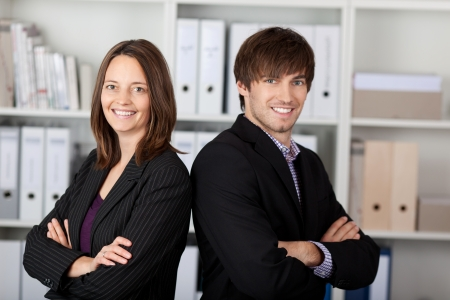 folded hands: Portrait of businessman and businesswoman with arms crossed standing in office