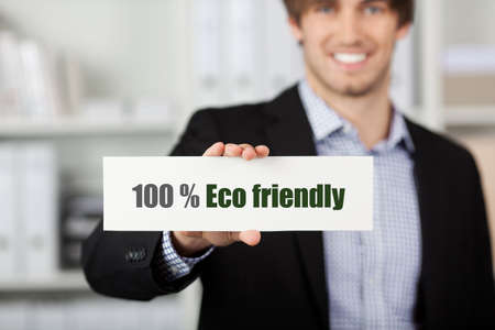 environmentalist label: Portrait of handsome young businessman holding Eco Friendly sign in office