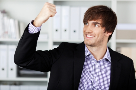 clenching fists: Handsome young businessman with clenched fist celebrating victory in office Stock Photo