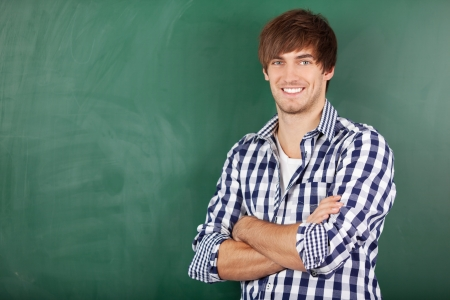 Portrait of handsome young male teacher with arms crossed standing against chalkboard Stock Photo - 21204525