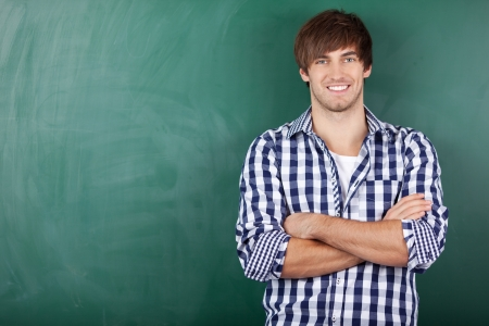 Portrait of handsome young male student with arms crossed standing against chalkboard Stock Photo - 21204561